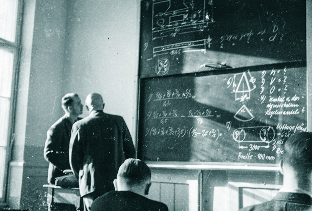 Students study an equation on a chalk board
